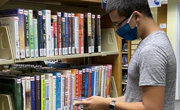 white man browsing new books wearing mask